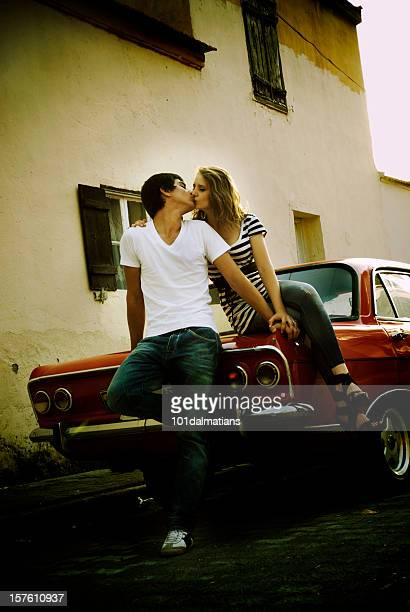 Young happy couple with old style car