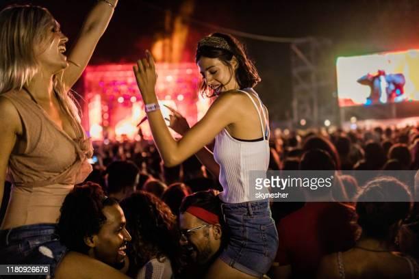 pares felizes novos que têm o divertimento no festival da música em a noite. - show de música popular - fotografias e filmes do acervo