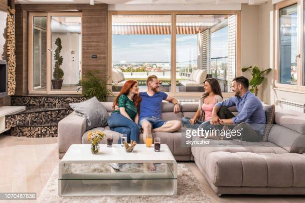 young happy couples relaxing in a penthouse and communicating. - four people stock pictures, royalty-free photos & images