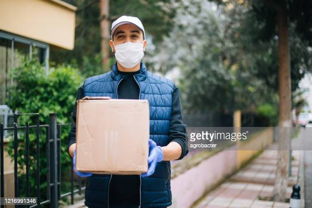 young happy delivery man with protective mask looking at camera - face mask protective workwear stock pictures, royalty-free photos & images