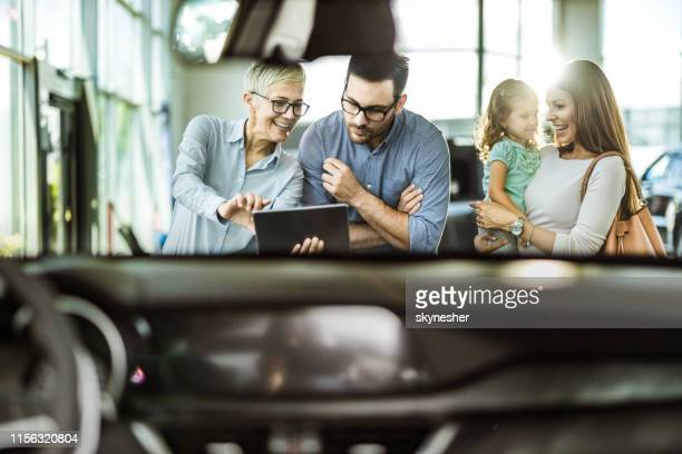 young happy family and female salesperson using digital tablet in a car showroom. - showroom stock pictures, royalty-free photos & images