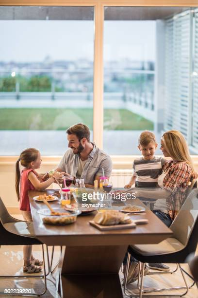 young happy family communicating and enjoying in dining room. - penthouse girls stock pictures, royalty-free photos & images
