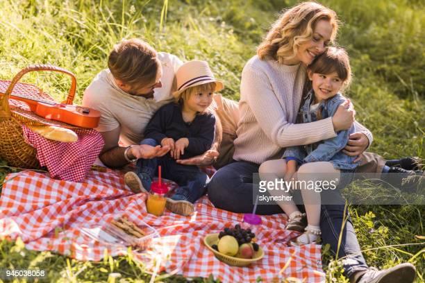 Junge glückliche Familie genießen tagsüber Picknick in der Natur.