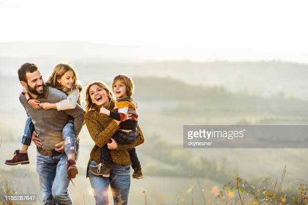 young happy family enjoying in autumn walk on a hill. - piggyback stock pictures, royalty-free photos & images