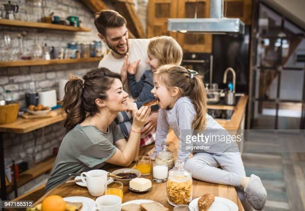 jonge gelukkige familie genieten van ontbijt tijdig in de keuken. - snack stockfoto's en -beelden
