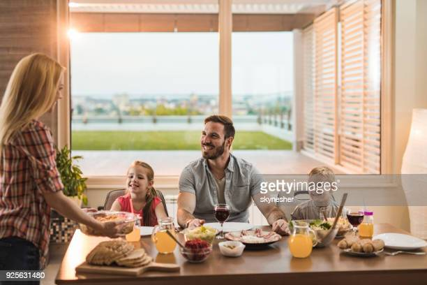 young happy family enjoying in lunch at their penthouse. - penthouse girls stock pictures, royalty-free photos & images