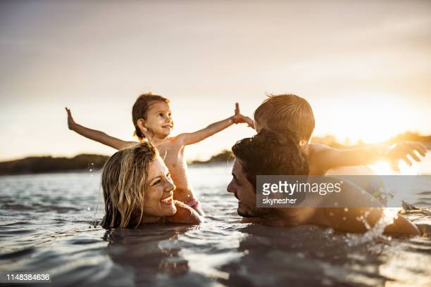 young happy family enjoying in sea at sunset. - island stock pictures, royalty-free photos & images