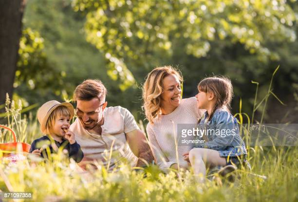 Young happy family enjoying on picnic during spring day in the forest.