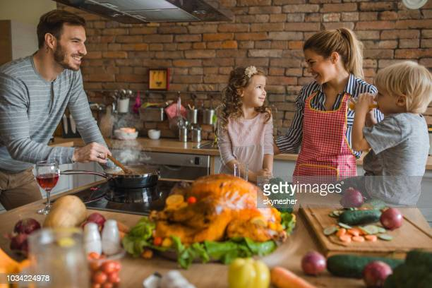 young happy family enjoying while preparing meal for thanksgiving in the kitchen. - happy thanksgiving stock photos and pictures