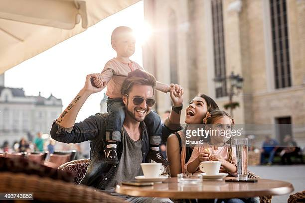 Young happy family having fun together in a cafe.