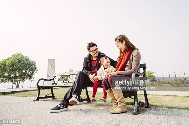 A young happy family having snacks in park