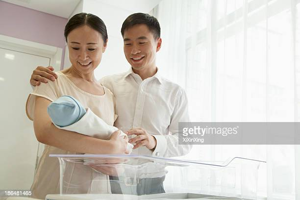 Young happy family holding their newborn in the hospital nursery