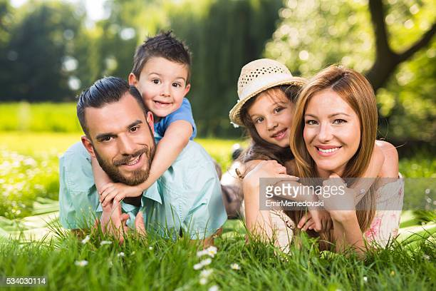 Junge glückliche Familie liegend auf dem Rasen in Natur.