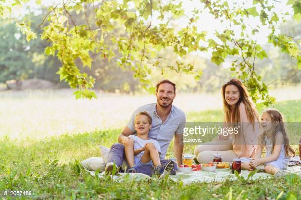 Junge glückliche Familie von vier auf ein Picknick in der Natur