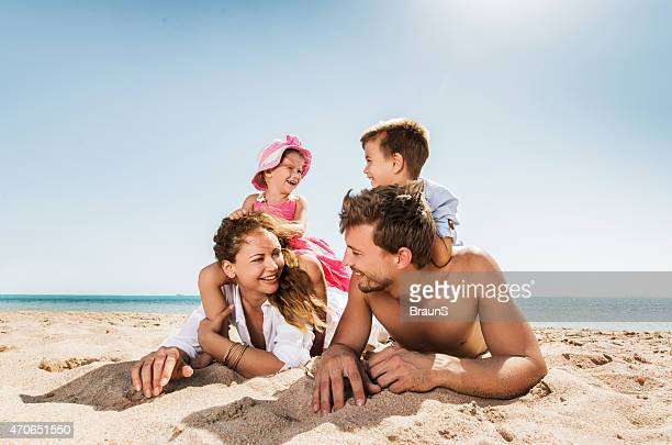 Young happy family relaxing at the beach and talking.