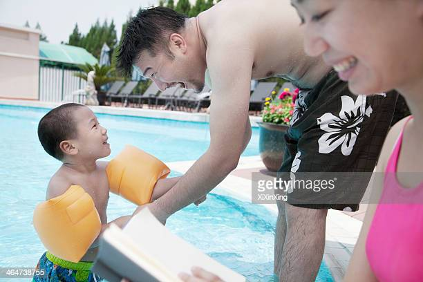 Young happy family relaxing by the pool on vacation