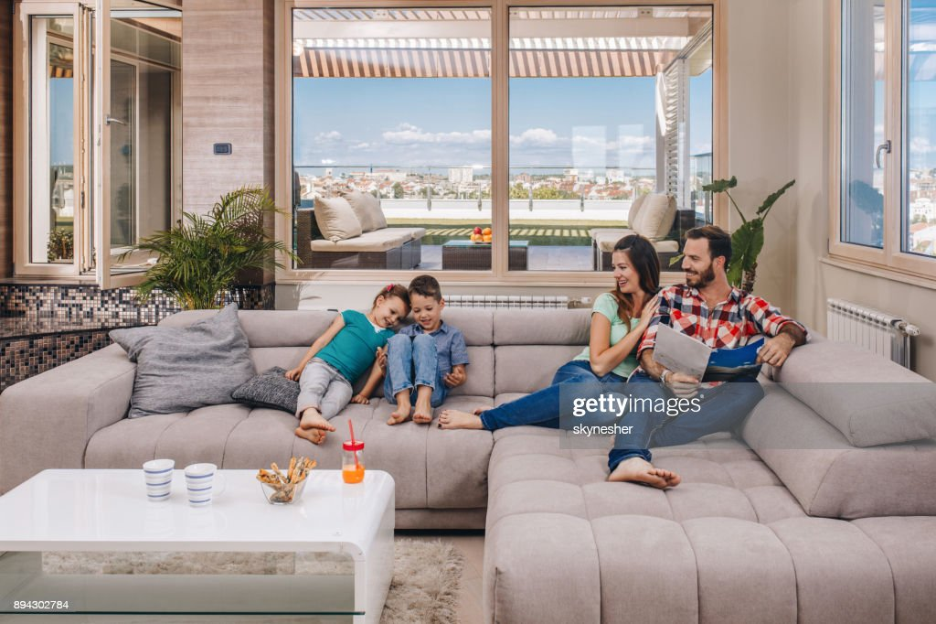 Young Happy Family Relaxing In The Living Room Of Their ...