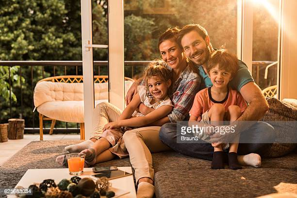 Young happy family relaxing on sofa at home.
