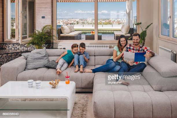 young happy family relaxing on sofa at their penthouse. - penthouse girls stock pictures, royalty-free photos & images