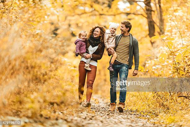 Young happy family taking a walk during autumn day.