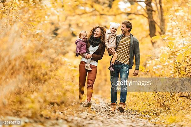 Jeune famille heureus'en prenant une promenade en automne.