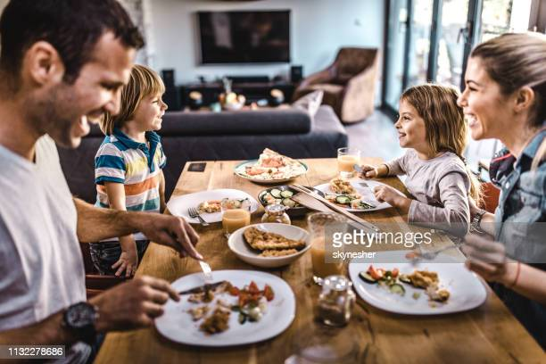 young happy family talking while having lunch at dining table. - simple living stock pictures, royalty-free photos & images