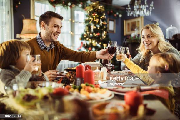 young happy family toasting during new year's dinner at dining table. - evening meal stock pictures, royalty-free photos & images