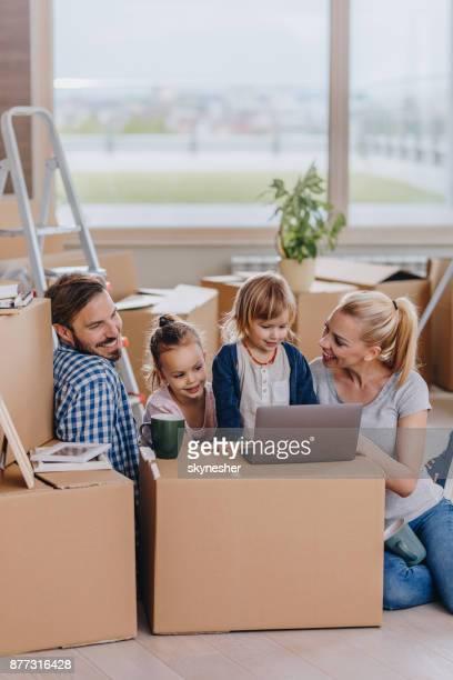 Junge glückliche Familie mit Laptop beim Umzug in neue Penthouse.