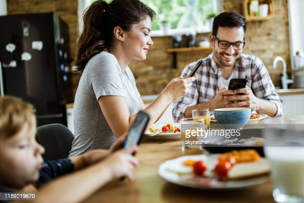 young happy family using mobile phones during breakfast at dining table. - candid forum stock pictures, royalty-free photos & images