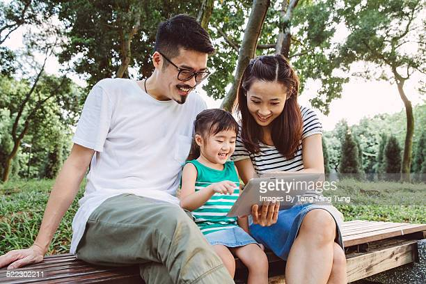 A young happy family using tablet joyfully