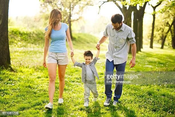 jovem feliz família andar pelo parque segurando as mãos. - in the park day 3 imagens e fotografias de stock