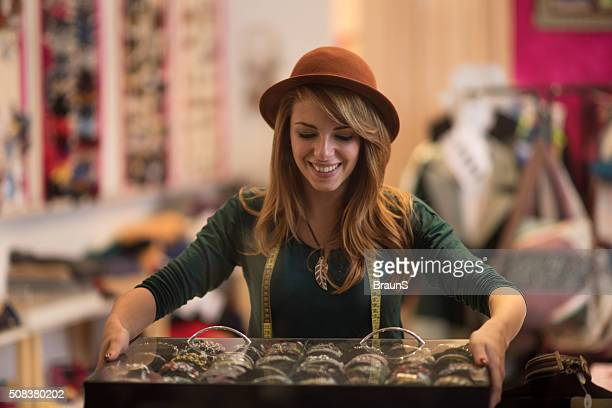 Young happy fashion designer working in her store.