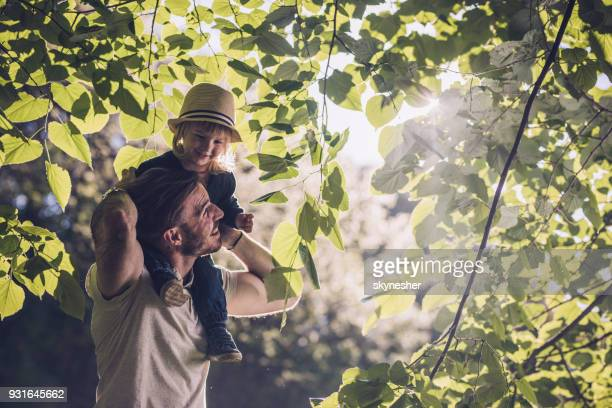 Young happy father and son having fun among tree branches in nature.