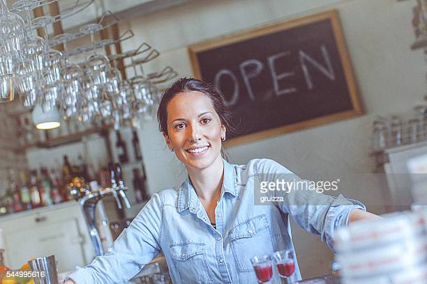 young happy female bar owner posing at the bar counter - opening event stock pictures, royalty-free photos & images