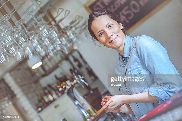 Young happy female bar owner posing at the bar counter