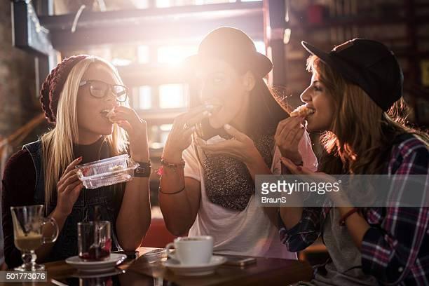 Joven feliz mujer amigos teniendo un refrigerio en un café.