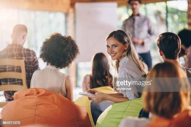 junge glücklich freiberufler notizen während business-präsentation im konferenzraum. - seminar stock-fotos und bilder