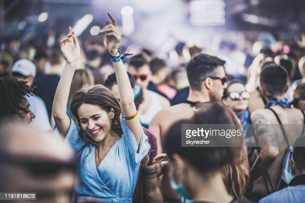 young happy friends dancing on a music festival. - music festival stock pictures, royalty-free photos & images