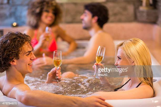 Young happy friends enjoying in champagne at hot tub and communicating.