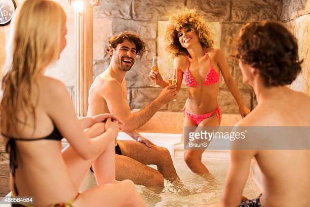 Young happy friends having fun in hot tub.