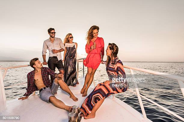 Young happy friends relaxing on a yacht and communicating.