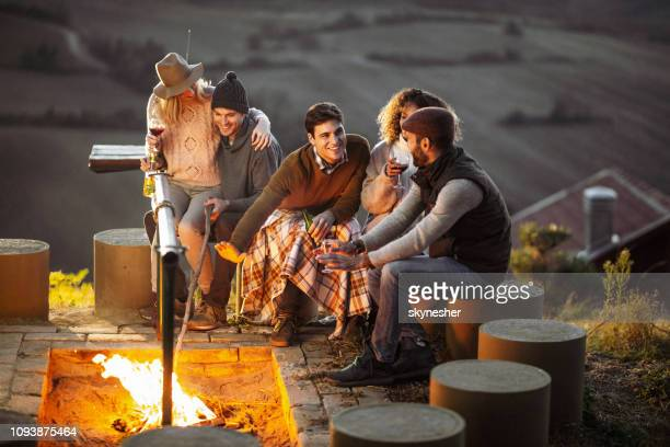 young happy friends talking by the bonfire in autumn. - warming up stock pictures, royalty-free photos & images