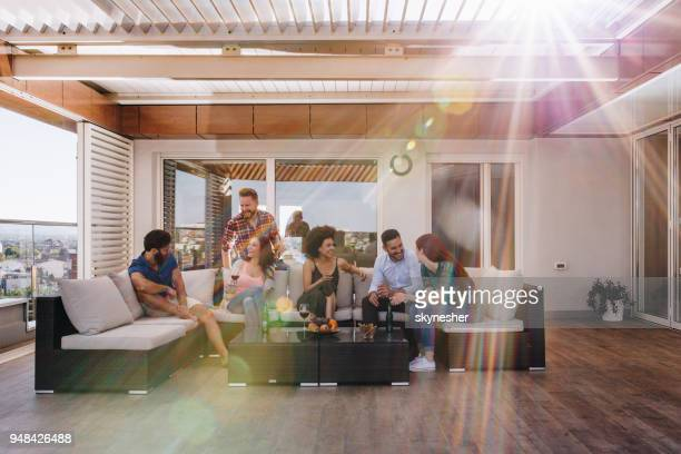 young happy friends talking on a penthouse patio. - patio stock pictures, royalty-free photos & images