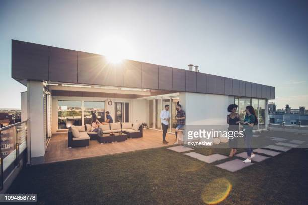 young happy friends talking while spending their time on a penthouse terrace. - penthouse stock pictures, royalty-free photos & images