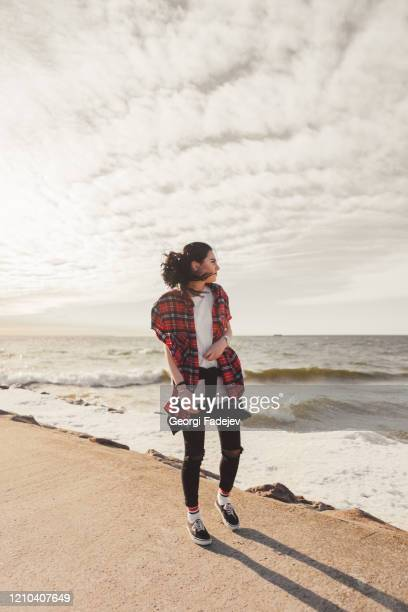 young happy girl in red wearing a checkered shirt walks on the beach. wide-open shirt. awesome atmosphere, spring time. - bicolore colore foto e immagini stock