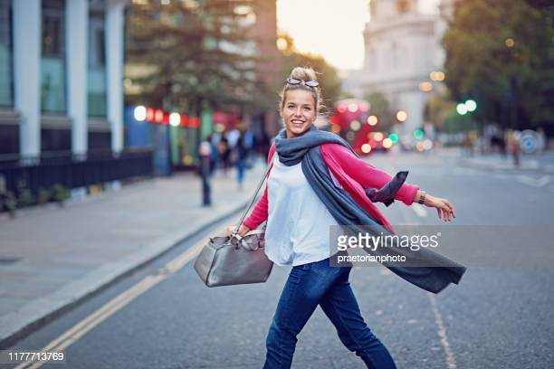 young, happy girl is crossing the street - pedestrian stock pictures, royalty-free photos & images
