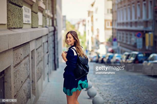 Young, happy girl is walking on the street in the city and turn around
