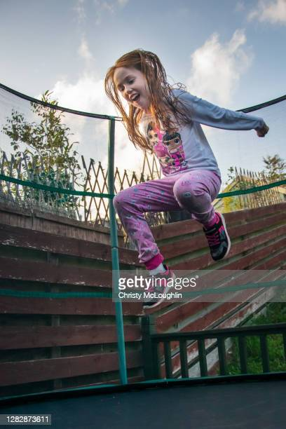 a young happy girl jumping in the air outdoors using garden trampoline - leinster province stock pictures, royalty-free photos & images