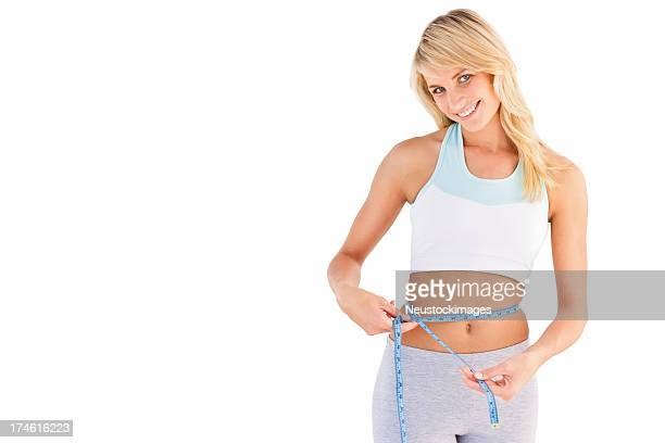 Young happy girl measuring her waist
