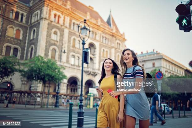 young, happy girls are crossing the street at the crosswalk - budapest stock pictures, royalty-free photos & images